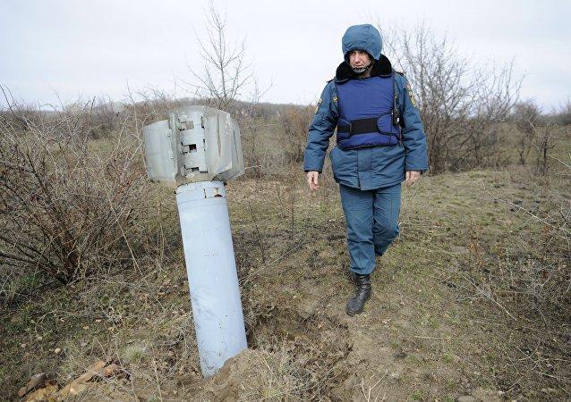 Funcionário do Ministério de Emergência da República Popular de Donetsk com míssil ucraniano (foto de arquivo)