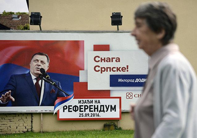 Mulher bósnia passa diante de um cartaz alusivo ao referendo na República Sérvia, 21 de setembro de 2016