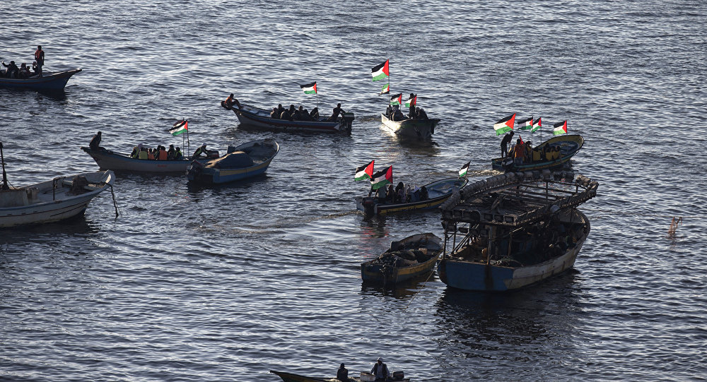 Palestinos velejam com a bandeira nacional no porto da Cidade de Gaza em apoio à flotilha de mulheres ativistas internacionais que tentam romper o bloqueio israelense à Faixa de Gaza - 5 de outubro de 2016