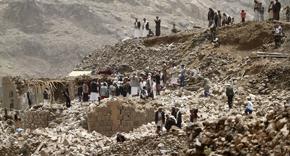 Moradores sobre os escombros de casas destruídas após um ataque aéreo na vila de Okash, perto de Sanaa, no Iêmen