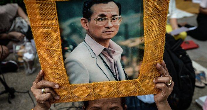 Apoiante do rei da Tailândia, Bhumibol Adulyadej, segura um retrato do rei perante o hospital Sriraj em Bangkok, Tailândia, 10 de outubro de 2016