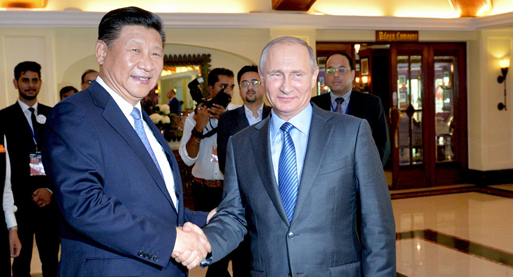 Presidente da China, Xi Jinping, e presidente da Rússia, Vladimir Putin, apertam as mãos às margens da Cúpula dos BRICS em Goa
