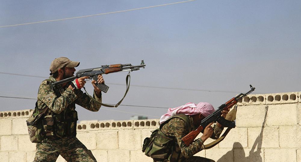 Esta foto de 11 de outubro de 2015 mostra dois militares do Exército Árabe Sírio durante um combate na cidade de Achan, província de Hama