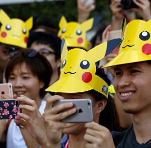 Pessoas vestidas de chapéus de 'Picachu' tiram fotos durante a parada dos fãs de Pokemon Go