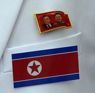 Broche com as imagens de Kim Il Sung e Kim Jong Il, respectivamente, fundador e atual líder da Coreia do Norte, junto à bandeira do país.