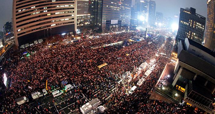 Sul-coreanos seguram velas durante uma manifestação contra a presidente Park Geun-hye em uma das avenidas principais de Seul, Coreia do Sul, 26 de novembro de 2016