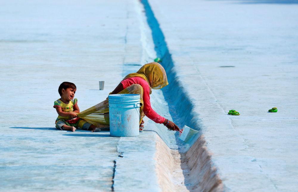 Uma mulher pinta um aqueduto enquanto sua filha tenta chamar sua atenção em Deli, Índia