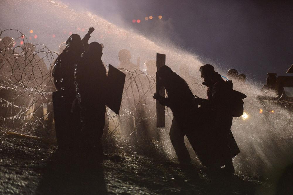 A polícia usa canhões de água para dispersar os protestantes contra a construção de um oleoduto em terras da reserva indígena de Standing Rock, em Dakota do Norte, em 20 de novembro de 2016