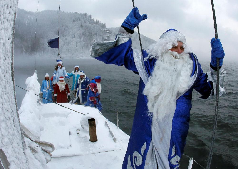 Membros do clube náutico Skipper, disfarçados do personagem da tradição russa Ded Moroz (Avô do Frio, ou Papai Noel), ao lado da neta do Papai Noel russo Snegurochka navegam ao longo do rio Enisei, marcando o fim da temporada de veleiros a 21 graus centígrados negativos, em 21 de novembro de 2016