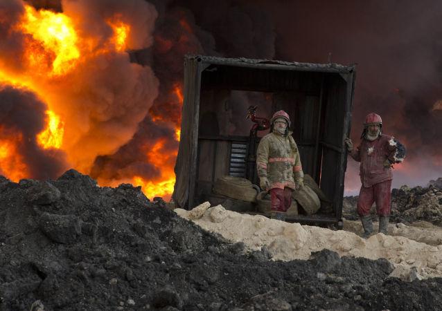Bombeiros apagam petróleo incendiado em Mossul, Iraque