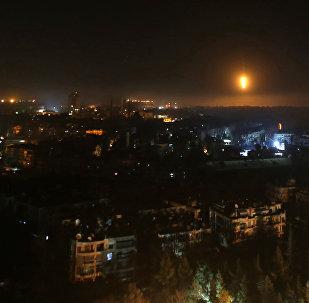 Cidade de Aleppo à noite durante lançamento de fogo pelas tropas sírias contra rebeldes na parte oriental da cidade, Síria, 5 de dezembro de 2016