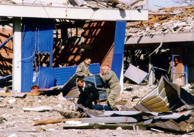 Trabalhadores limpam escombros de um centro de treinamento policial em Novi Sad, no norte da Iugoslávia, que foi destruída durante ataques aéreos da OTAN em 25 de março de 1999 (imagem de arquivo)
