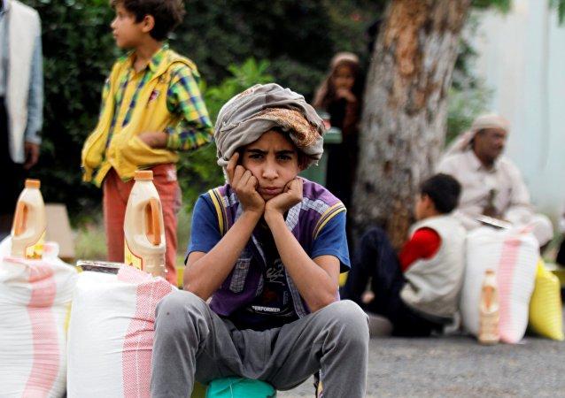 Um menino está sentando ao lado do alimento que ele recebeu de uma caridade local em Sanaa, Iêmen, junho 23, 2016