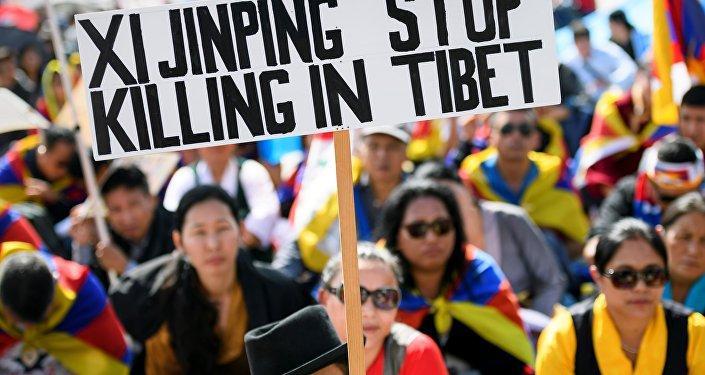 Manifestantes da comunidade tibetana na Europa com cartaz Xi Jinping, pare de matar no Tibete durante o protesto perante o edifício da ONU em Genebra, Suiça, 16 de setembro de 2016