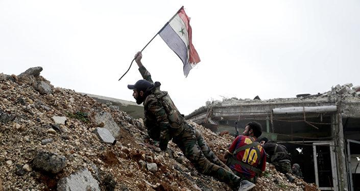 Soldado do exército sírio hasteia a bandeira nacional