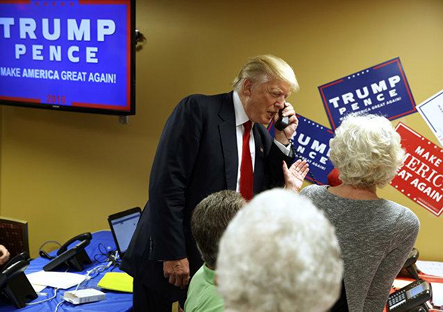 Presidente eleito dos EUA, Donald Trump, ao telefone, em visita a uma empresa de call center de Asheville, Carolina do Norte, durante campanha