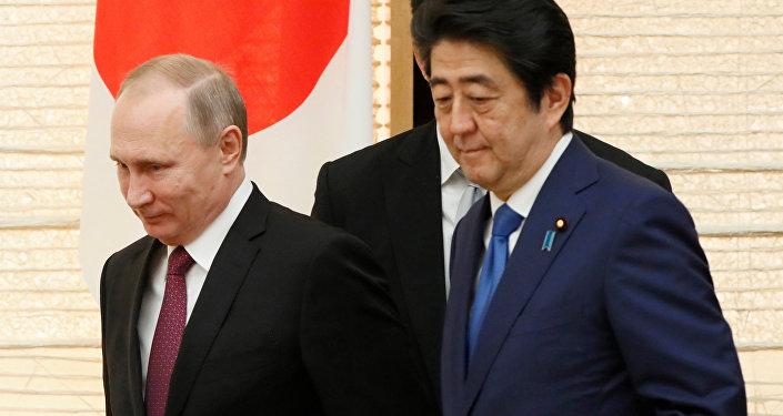O presidente russo Vladimir Putin anda com o primeiro-ministro japonês Shinzo Abe na chegada para um almoço de negociações em Tóquio, Japão, sexta-feira, 16 de dezembro de 2016