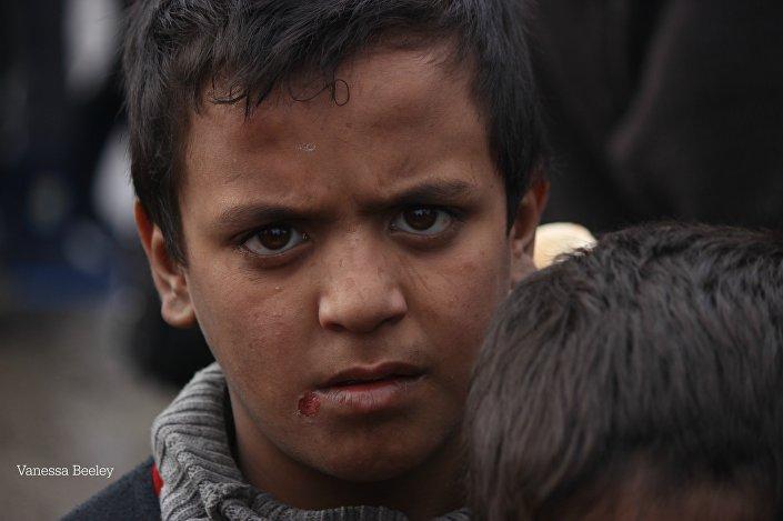 Menino com olhar exausto à espera do recebimento de comida em Aleppo oriental