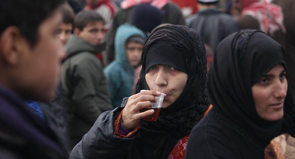Mulheres e crianças em um ponto de assistência em Aleppo oriental