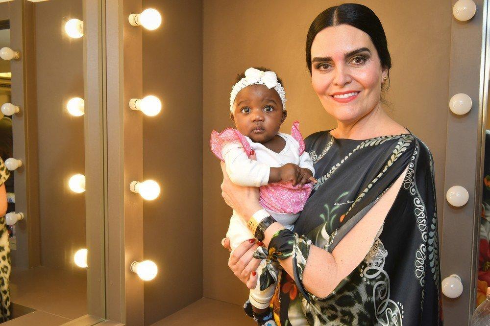 Daniela Guimarães e um bebê refugiado assistido pelo projeto