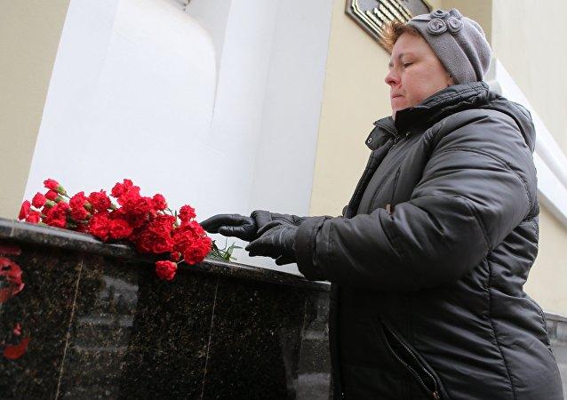 As pessoas estão depondo flores junto à sede do Ensamble Aleksandrov