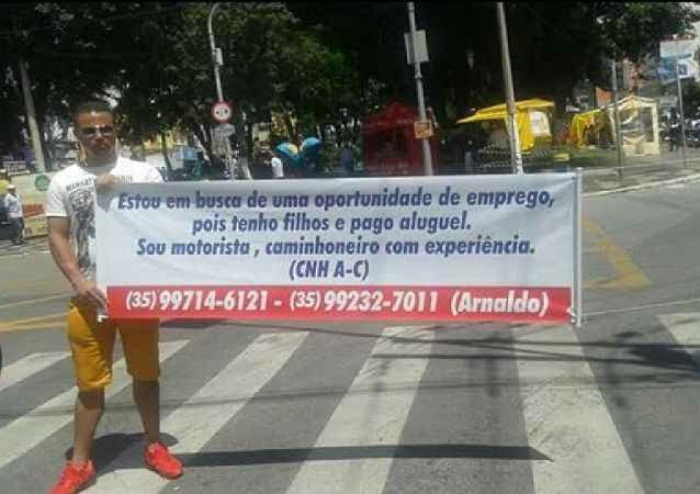 Motorista Arnaldo usa faixa para pedir emprego em Pouso Alegre (MG)