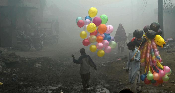 Criança carrega balões em subúrbio do Paquistão (arquivo)