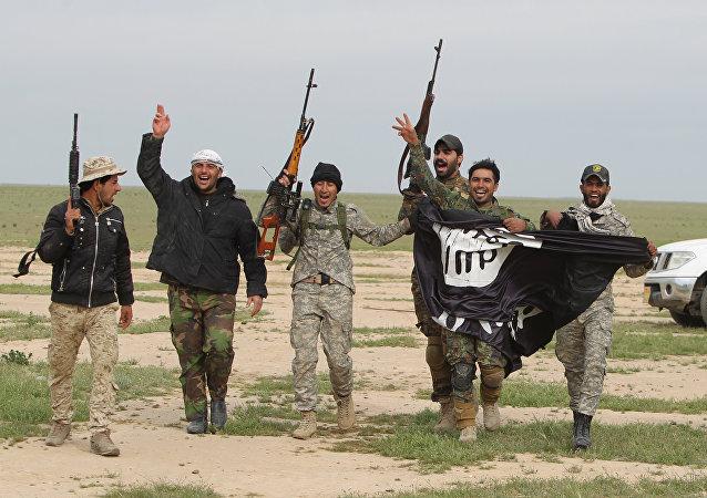 Membros das Forças de Mobilização Popular capturam bandeira do Daesh durante confrontos para retomar territórios de Samarra controlados por terroristas, 3 de março de 2016