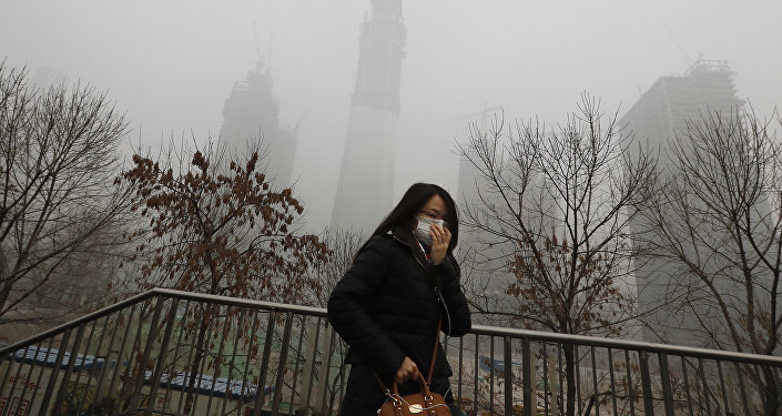 Uma mulher de máscara para a proteção contra a poluição do ar anda em uma ponteem Beijing enquanto a capital de China é encoberta pela fumaça pesada na terça-feira, dezembro 20, 2016