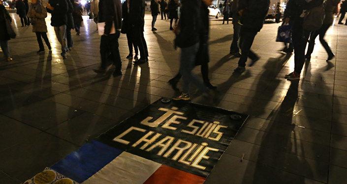 As pessoas passam por uma placa que diz Je suis Charlie (Eu sou Charlie) em homenagem das vítimas do atentado na redação da revista que occoreu em 7 de janeiro de 2015