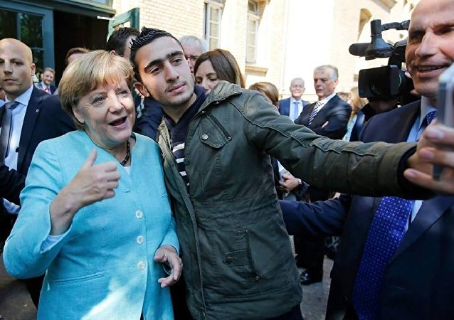 Anas Modamani, natural da capital síria, Damasco, tira um selfie com a chanceler alemã Angela Merkel junto ao centro para refugiados Spandau, em Berlim