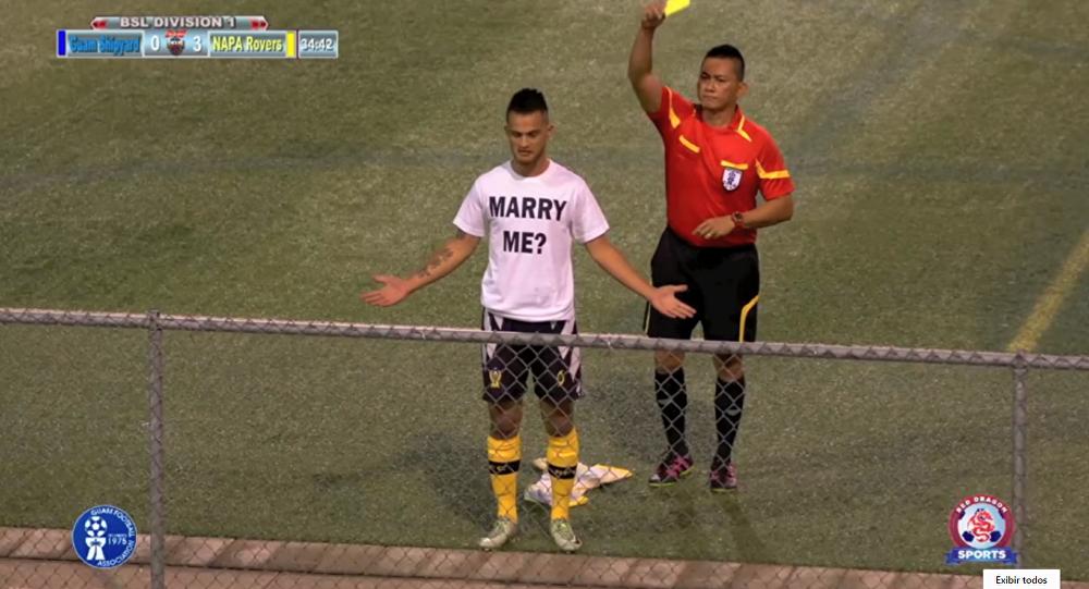 Depois de marcar um golaço de bicicleta, o jogador Ashton Surber, do clube Rovers, da ilha de Guam, pede a mão de sua amada em casamento e recebe cartão amarelo do árbitro.