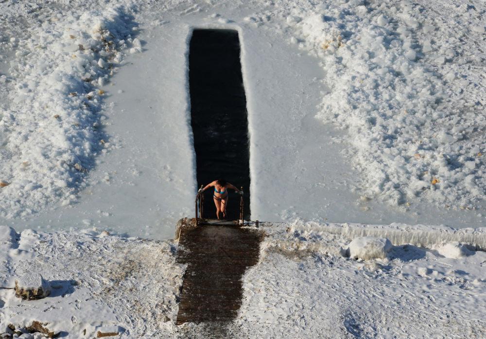 Mulher sai após mergulho em abertura no gelo na baía de Amur