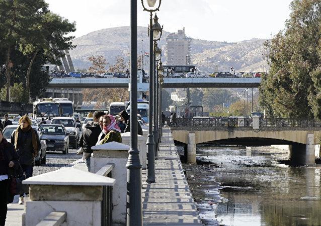Pessoas andando às margens do rio Barada na capital síria, Damasco, em 3 de janeiro de 2017
