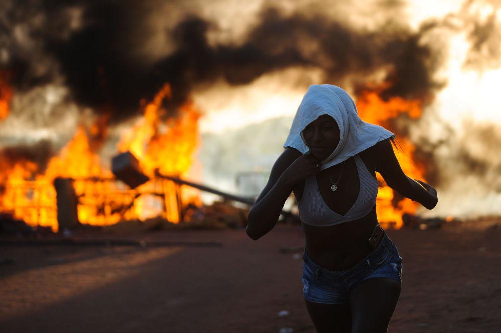 Menina corre durante protestos no Brasil