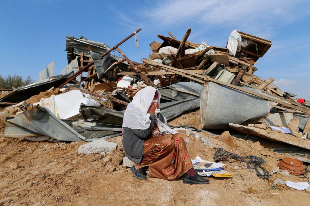 Mulher chorando perto da sua casa arruinada no deserto de Israel