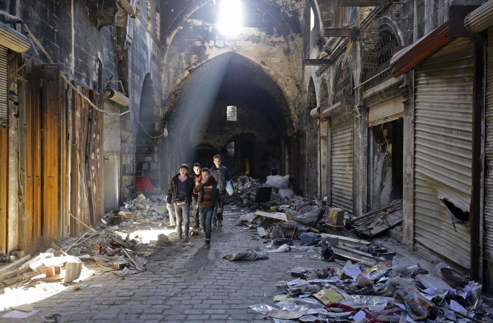 Crianças sírias passeiam pela parte velha da cidade de Aleppo, um mês após sua libertação.