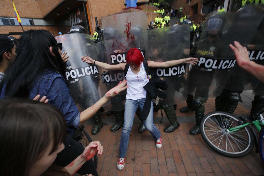 Moça tenta conter os policiais durante os protestos nas ruas de Bogotá, na Colômbia.