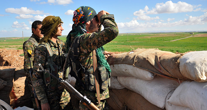 Membros das Unidades de Proteção do Povo do Curdistão (YPG) monitoram as posições do grupo do Estado Islâmico (Daesh) na cidade síria de Ras al-Ain, perto da fronteira turca em 13 de março de 2015