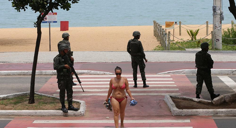 Uma mulher cruza uma via pública, guardada por soldados das Forças Armadas em Vitória, ES, em 8 de fevereiro