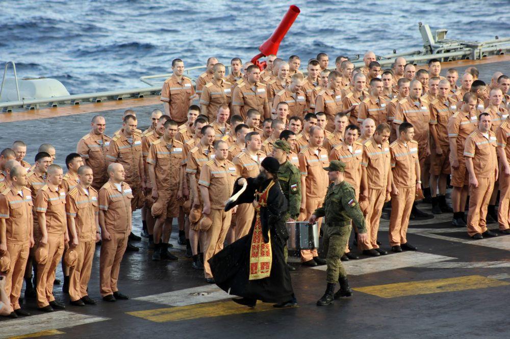 Padre e militares durante ritual religioso no convés do porta-aviões Admiral Kuznetsov no Atlântico