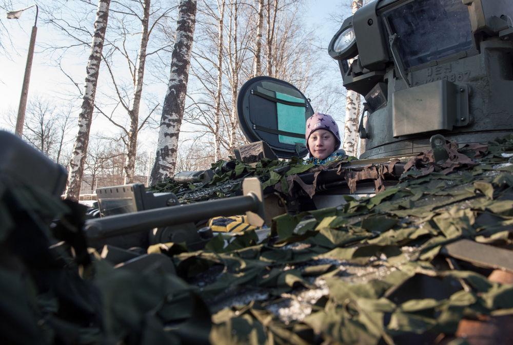 Menino no veículo ligeiro de reconhecimento FV107 SCIMITAR (Grã-Bretanha) durante a demonstração de material militar e armamento da OTAN na Letônia