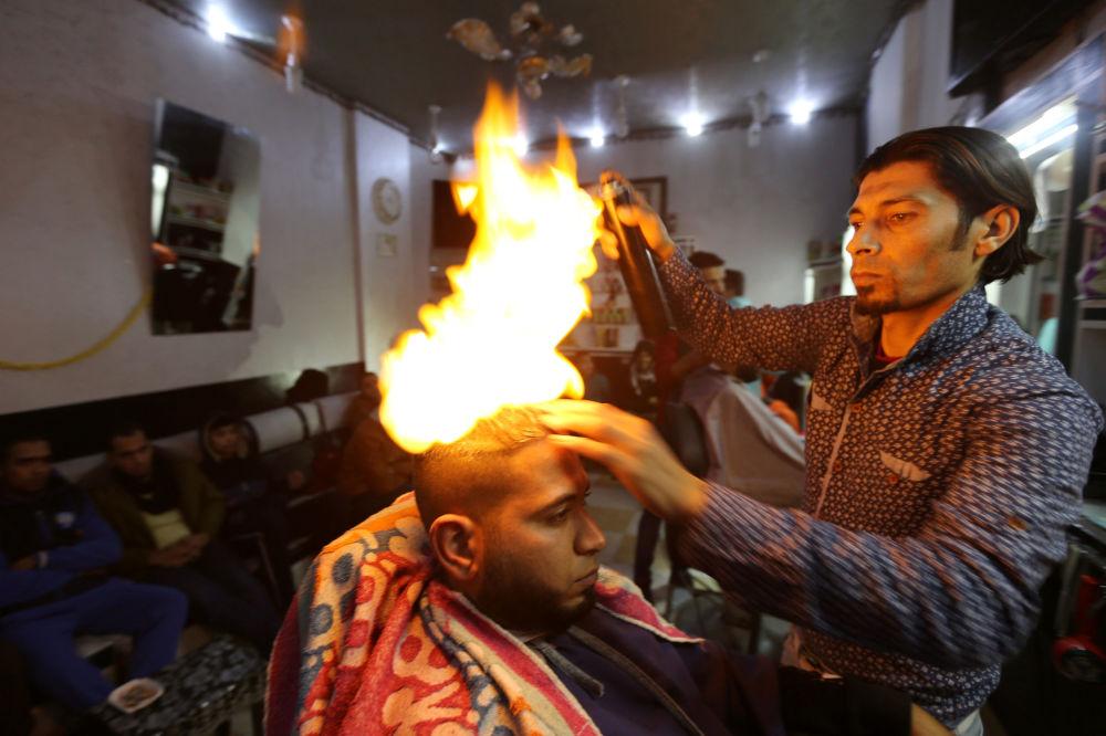 Barbeiro palestino Ramadan Odwan corta e arruma cabelo de um freguês usando fogo no seu salão situado na Faixa de Gaza.