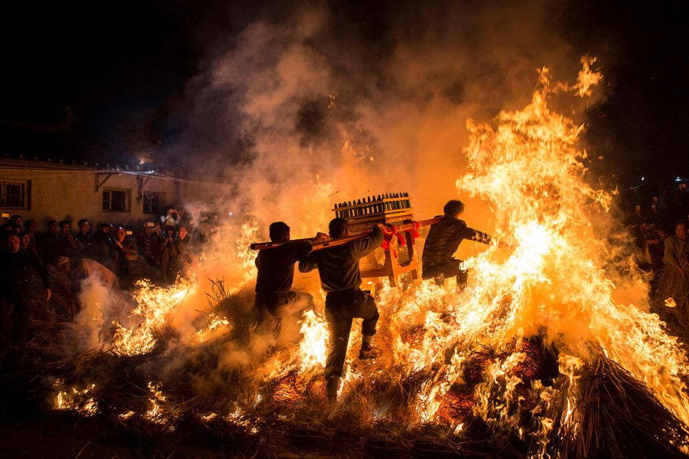 Homens carregando um andor funerário pulam por cima do fogo, o que garante boa sorte na celebração tradicional do Ano Novo chinês.
