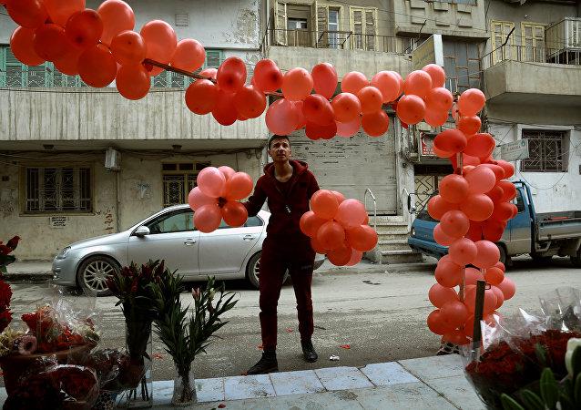 Homem sírio segura balões em frente de uma loja de venda de presentes para o Dia dos Namorados na cidade de Al-Qamishli, nordeste da Síria, 13 de fevereiro de 2017