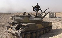 Foto publicada no Facebook em 5 de agosto pela Rased News Network, afiliada do Daesh, mostra um terrorista com bandeira do Daesh sobre um tanque capturado em combate ao exército sírio