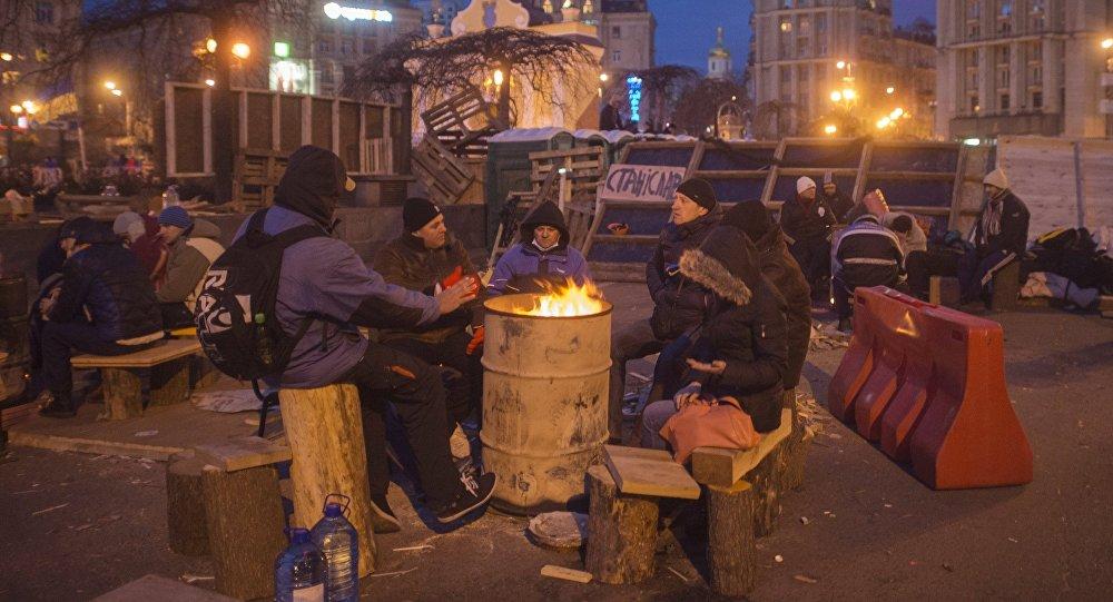 Apoiantes da adesão da Ucrânia à UE se aquecem perto de uma fogueira na Praça da Independência, Kiev, Ucrânia