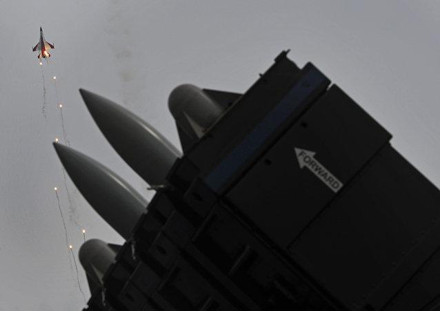 Mísseis Spyder superfície-ar em uma exposição estática são observados enquanto um jato F-16 da esquadrilha acrobática da Força Aérea de Cingapura, Cavaleiros Negros, lança foguetes luminosos no quarto dia do Singapore Air Show em Cingapura, na sexta-feira, 14 de fevereiro de 2014
