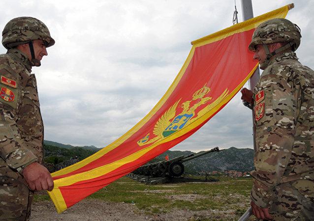 Soldados de artilharia do exército montenegrino olham para a bandeira do Montenegro durante as preparações na véspera do Dia da Independência, em 20 de maio de 2010, em Cetinje