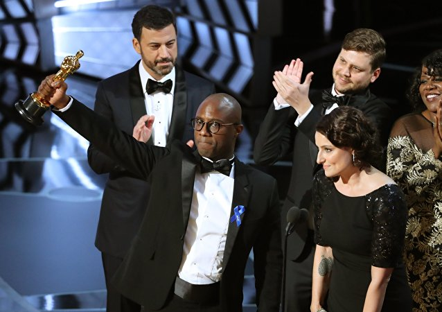 89th Academy Awards - Oscars Awards Show - Hollywood, California, U.S. - 26/02/17 - Writer and Director Barry Jenkins of Moonlight holds up the Best Picture Oscar in front of host Jimmy Kimmel (rear) as he stands with Producer Adele Romanski (R).